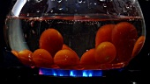 Dropping tomatoes into boiling water