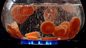 Carrot slices being cooked in hot water