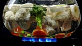 Mixed vegetables falling into boiling water