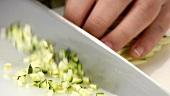 Zucchinistifte in Würfel schneiden