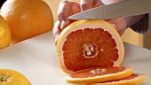 Slicing pink grapefruit