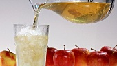 Pouring apple juice into a glass of crushed ice