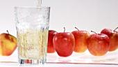 Apfelsaft in ein Glas mit Eiswürfeln gießen
