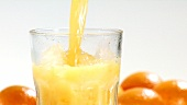 Pouring orange juice into a glass of crushed ice (close-up)