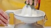 Limette mit elektrischer Zitruspresse auspressen