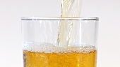 Pouring apple juice into a glass (close-up)