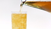 Pouring apple juice out of a jug into a glass of crushed ice