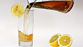 Pouring apple juice into a glass with a slice of lemon
