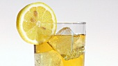 Pouring apple juice into a glass of ice cubes with a slice of lemon