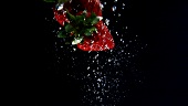 Strawberries floating in water (black background)