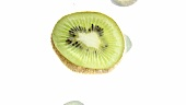 Slices of kiwi fruit floating in water (white background)