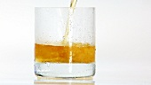 Pouring whisky into a glass of crushed ice