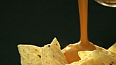 Pouring cheese dip over tortilla chips