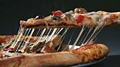 Ein Pizzastück, das Fäden zieht, anheben