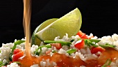 Rice with chilli sauce and lime wedges