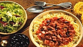Spaghetti with meat and tomato sauce, black olives and salad leaves