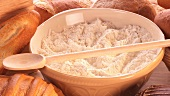 A bowl of flour, various types of bread and bread rolls