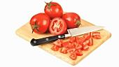 Ganze und aufgeschnittene Tomaten mit Messer auf Holzbrett