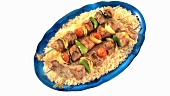 Shashlik (meat and vegetable kebabs) on rice