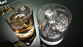 Pouring whisky into two glasses containing ice cubes