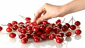 A pile of cherries and a hand taking one
