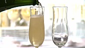 Champagne being poured into two glasses