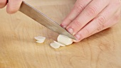 Knoblauchzehe in dünne Scheiben schneiden