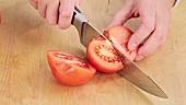 Tomate in grobe Würfel schneiden