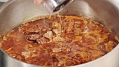 Seasoning beef goulash with salt and pepper