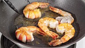 Frying and turning prawns in a pan