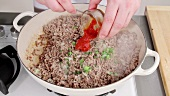 Mixing browned minced meat with tomato puree