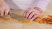 Chopping orange peel into fine strips