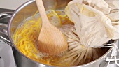 Boiling orange juice and orange peel with pith and pips in a muslin cloth