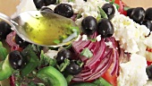 Vinaigrette being drizzled over Greek salad