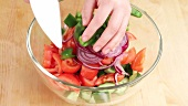 Ingredients for vegetable salad being placed in a bowl
