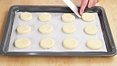 Pastry circles (for scones) being placed on a baking tray lined with grease-proof paper