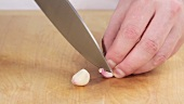 Garlic being peeled and sliced