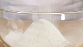 Flour being sieved into a bowl