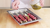 Lamb kebabs being brushed with herb marinade