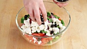 Olives being added to a salad with feta