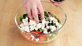 Oliven auf den Salat mit Feta verteilen