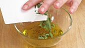Oregano leaves being added to dressing
