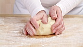 Pastry being kneaded on a floured work surface