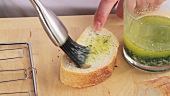 Baguette slices being brushed with liquid garlic butter