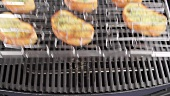 A grill rack of garlic baguette slices being removed from the grill