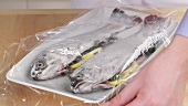 Vorbereitete Kräuterforellen mit Klarsichtfolie abdecken