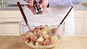 Ingredients for potato salad being seasoned and mixed