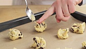 Balls of chocolate chip dough being placed on a baking tray