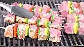 Meat and vegetable kebabs being turned on a grill