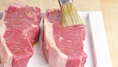 New York strip steaks being brushed with oil